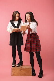 Portrait de jolies filles en uniforme scolaire, lire des livres, debout isolé sur mur rouge