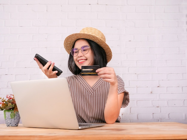 Portrait de jolies jeunes femmes fait des achats en ligne et paie par carte de crédit.