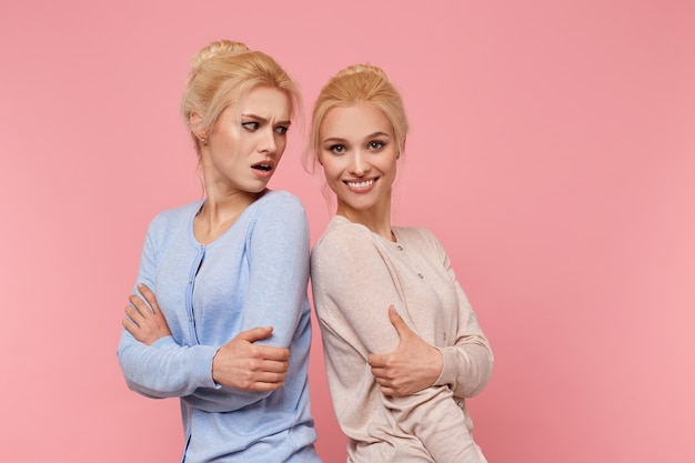 Portrait de jolies jumelles blondes, la fille est offensée par sa sœur qu'elle pose mieux qu'elle, a l'air insatisfaite, elle sourit et regarde la caméra. les filles se tiennent sur fond rose.