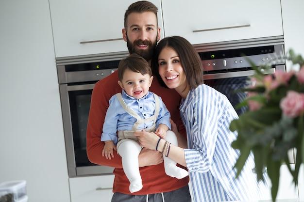 Portrait de jolis jeunes parents avec bébé regardant la caméra dans la cuisine à la maison.
