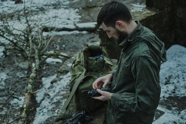 Portrait d'un joueur d'airsoft dans un équipement professionnel charge une arme à feu avec des balles dans la forêt. soldat avec des armes en guerre