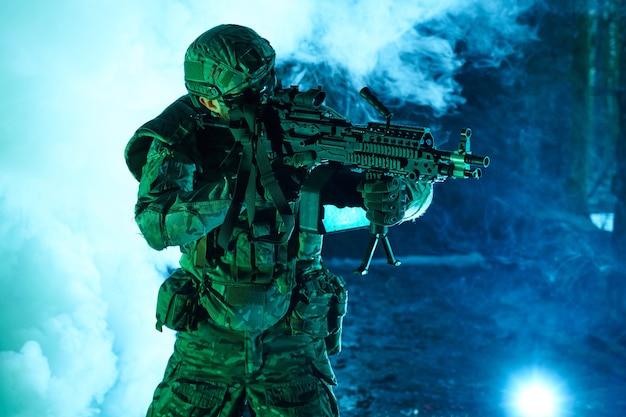 Portrait d'un joueur d'airsoft dans un équipement professionnel avec une mitrailleuse dans un bâtiment en ruine abandonné. soldat avec des armes en guerre dans la fumée et le brouillard
