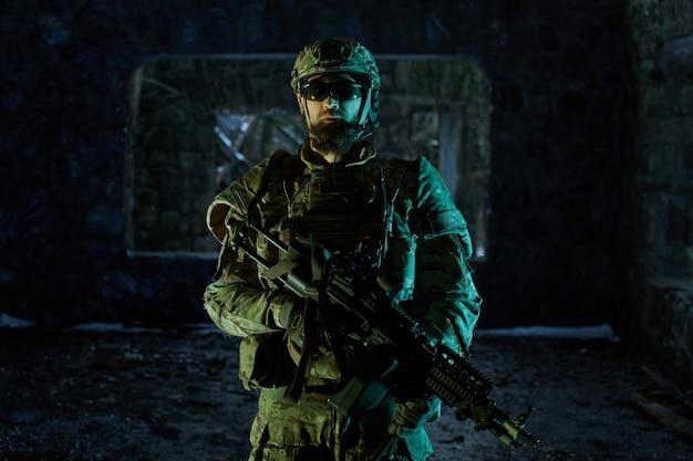 Portrait d'un joueur d'airsoft dans un équipement professionnel avec une mitrailleuse dans un bâtiment en ruine abandonné. soldat avec des armes en guerre