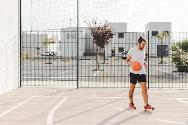 Portrait d'un joueur de baskeball debout devant un tribunal