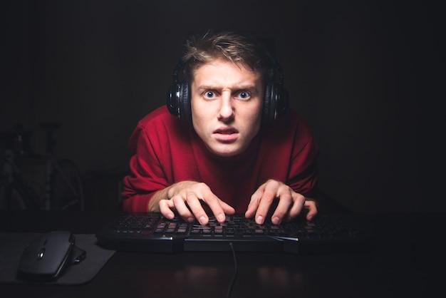 Portrait de joueur concentré en regardant le jeu et en utilisant un clavier d'ordinateur