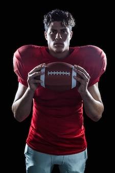 Portrait de joueur de football américain déterminé avec ballon debout sur fond noir