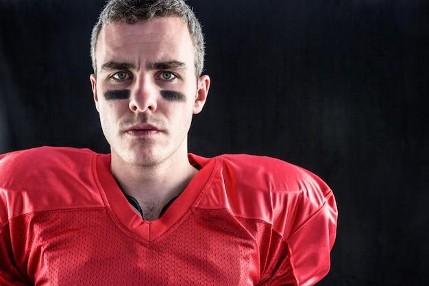 Portrait d'un joueur de football américain sérieux regardant la caméra