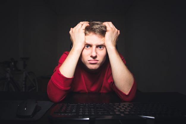 Portrait d'un joueur frustré en regardant un écran d'ordinateur avec une expression de visages tristes