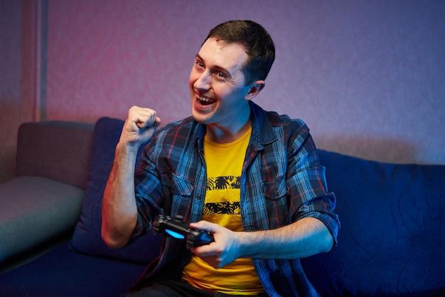 Portrait de joueur ludique fou, garçon appréciant jouer à des jeux vidéo à l'intérieur assis sur le canapé, tenant la manette de jeu de la console dans les mains. repos à la maison, bon week-end