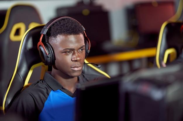 Portrait d'un joueur masculin de cybersport africain portant des écouteurs jouant à des jeux vidéo, participant à un tournoi esport alors qu'il était assis dans un club de jeu ou un cybercafé
