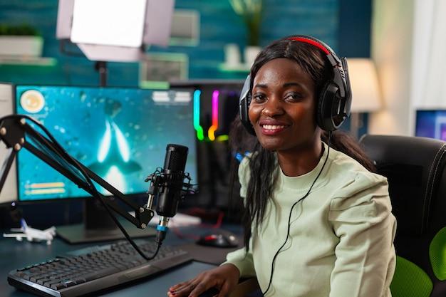 Portrait d'un joueur professionnel africain de streamer e regardant la caméra. diffusez des jeux vidéo viraux pour vous amuser en utilisant des écouteurs et un clavier pour le championnat en ligne.