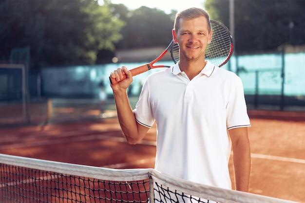 Portrait de joueur de tennis masculin positif avec raquette debout à terre battue près de net