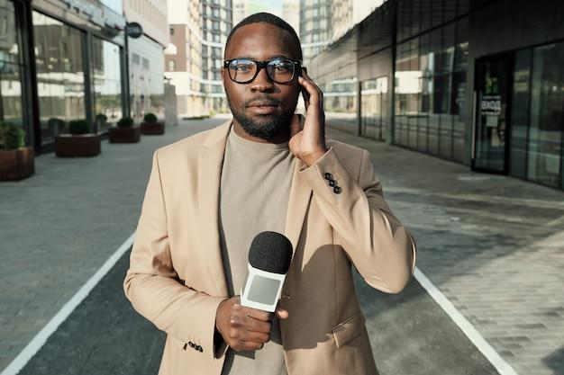 Portrait de journaliste africain debout avec microphone et regardant la caméra pendant son travail dans la ville