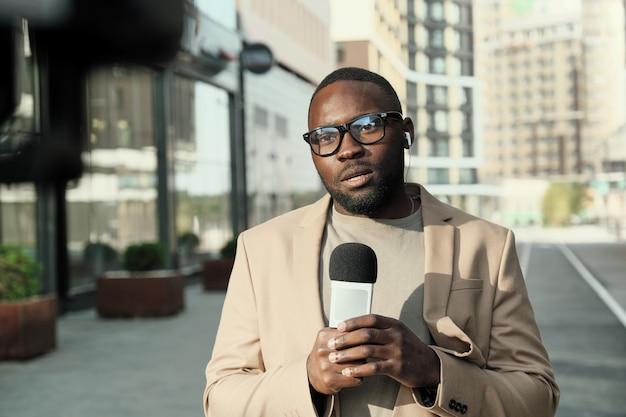 Portrait de journaliste africain à lunettes parlant au microphone tout en travaillant dans la ville