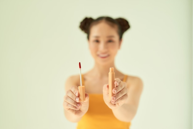 Portrait de joyeuse belle femme asiatique montrant le rouge à lèvres sur fond clair.