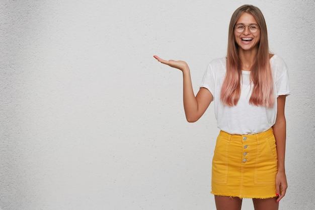 Portrait de joyeuse belle jeune femme étudiant porte t-shirt, jupe jaune et lunettes se sent heureux et détient copyspace sur palm isolé sur mur blanc