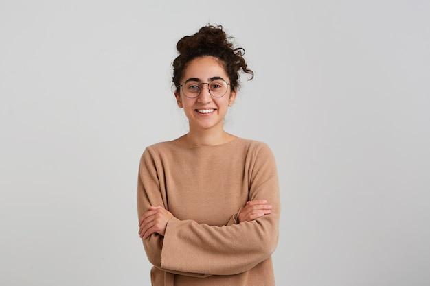Portrait de joyeuse belle jeune femme étudiante avec chignon de cheveux bouclés foncés