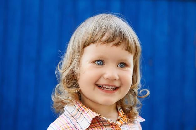 Portrait de joyeuse belle petite fille joyeuse contre le vieux mur bleu texturé