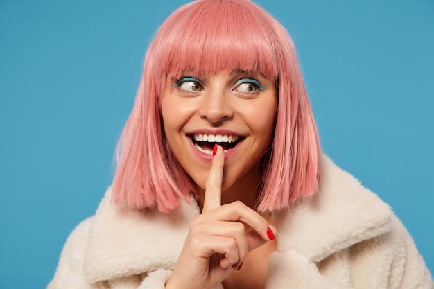 Portrait de joyeuse excitée belle jeune femme aux cheveux rose avec un maquillage de fête souriant largement tout en regardant de côté, levant l'index à sa bouche en geste silencieux, isolé