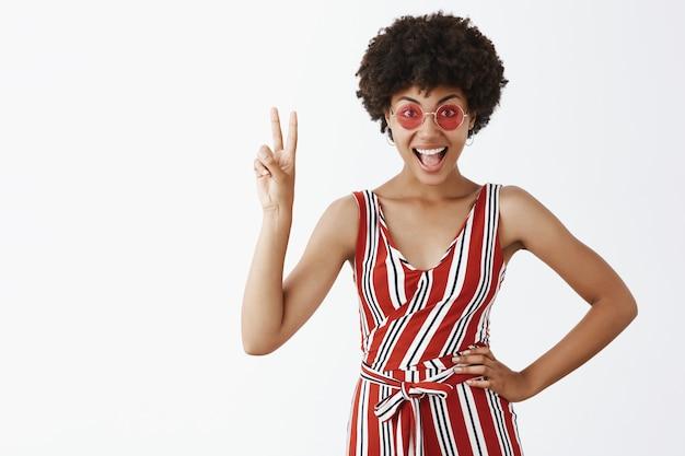 Portrait de joyeuse femme afro-américaine émotive et élégante en lunettes de soleil à la mode et salopette rayée montrant le signe de la victoire avec la main levée et souriant