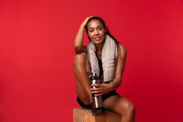 Portrait de joyeuse femme afro-américaine en vêtements de sport noir assis sur une boîte avec une serviette et une bouteille d'eau, isolé sur mur rouge