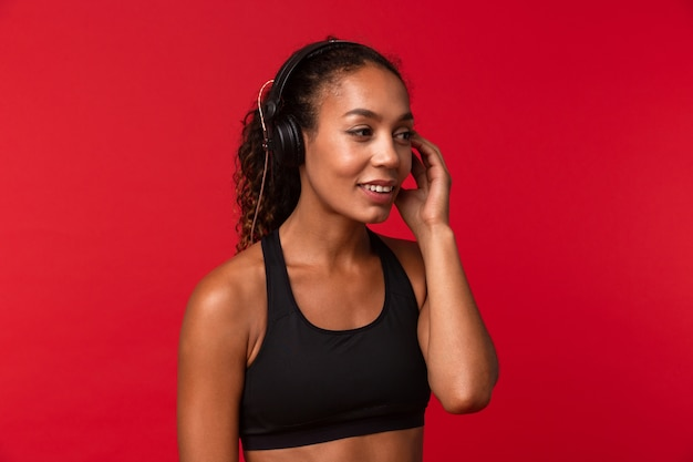 Portrait de joyeuse femme afro-américaine en vêtements de sport noir, écouter de la musique à l'aide d'un casque, isolé sur mur rouge