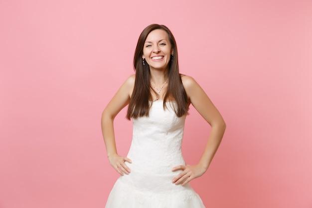 Portrait de joyeuse femme souriante en belle robe blanche debout avec les bras sur les hanches