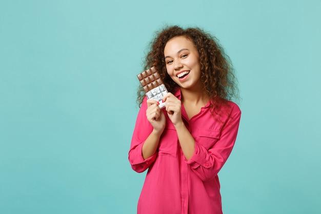 Portrait de joyeuse fille africaine dans des vêtements décontractés tenant à la main une barre de chocolat isolée sur fond de mur bleu turquoise en studio. les gens émotions sincères, concept de style de vie. maquette de l'espace de copie.