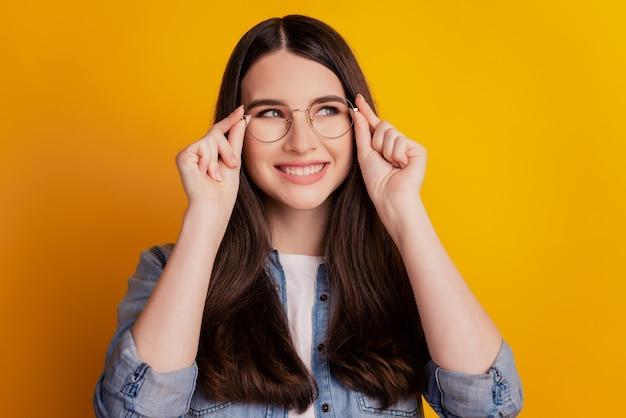 Portrait de joyeuse fille de mode souriante ajuster les lunettes sur fond jaune