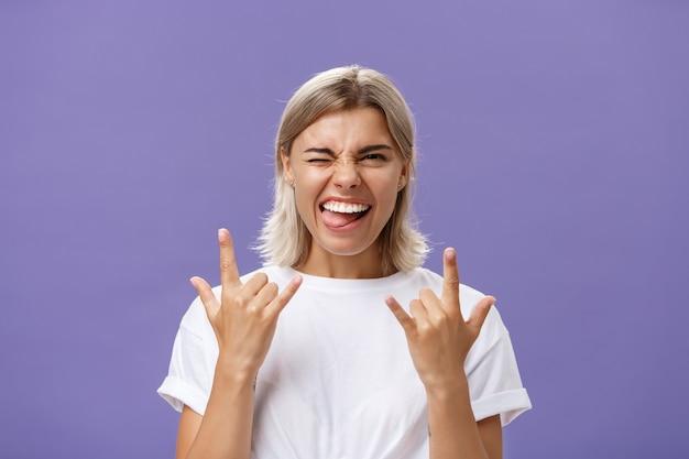 Portrait de joyeuse heureuse belle femme élégante avec une coupe de cheveux moyenne blonde un clin de œil souriant et qui sort la langue tout en montrant le geste rock-n-roll avec les deux mains sur le mur violet