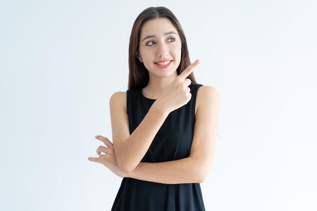 Portrait de joyeuse jeune femme d'affaires indiquant la direction