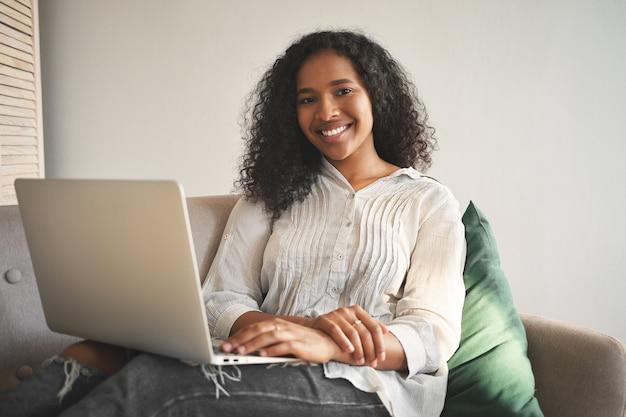Portrait de joyeuse jeune femme africaine en jeans et chemise souriant largement tout en surfant sur internet sur un ordinateur portable générique, bénéficiant d'une connexion sans fil haut débit dans le salon