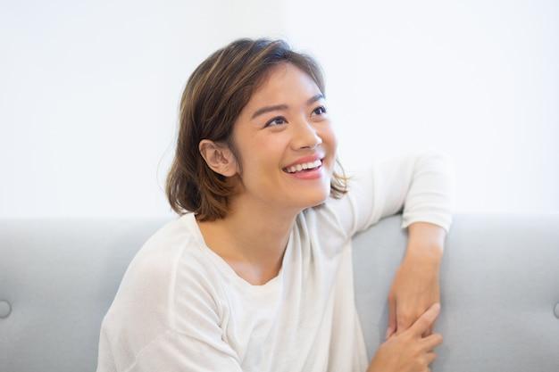 Portrait de joyeuse jeune femme assise sur l'entraîneur à la maison