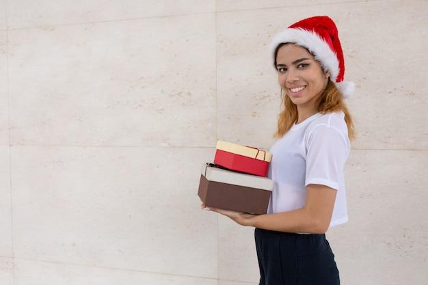 Portrait de joyeuse jeune femme en bonnet de noel avec des coffrets cadeaux