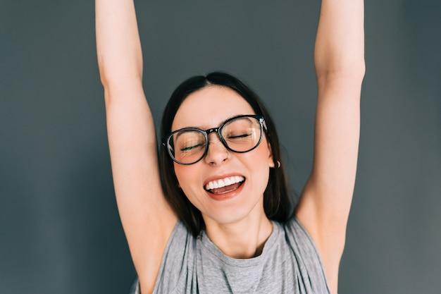 Portrait de joyeuse jeune femme caucasienne à lunettes mettant les mains