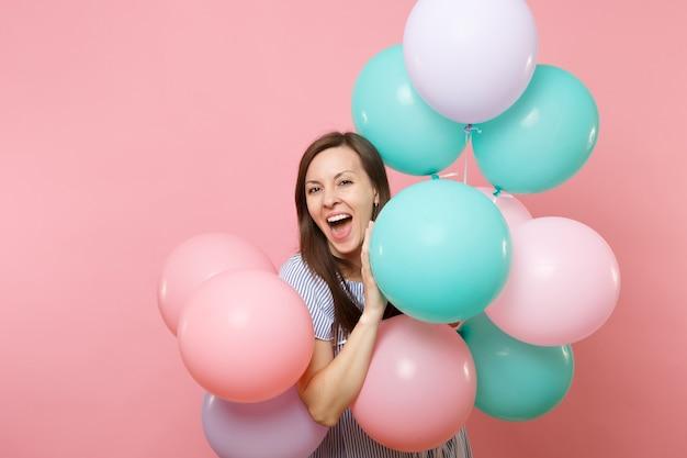 Portrait de joyeuse jeune femme heureuse avec la bouche ouverte en robe bleue tenant des ballons à air colorés isolés sur fond rose tendance lumineux. fête d'anniversaire, concept d'émotions sincères.