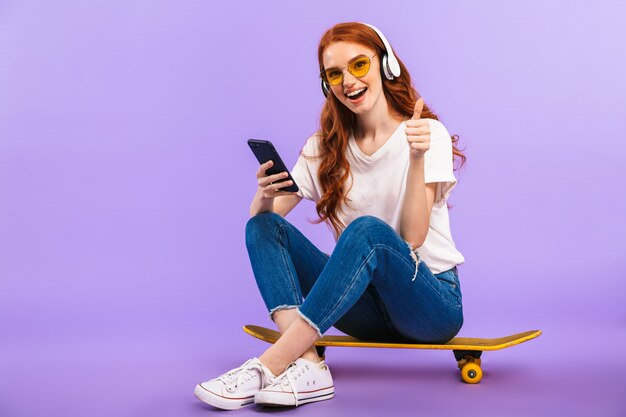 Portrait d'une joyeuse jeune femme à lunettes de soleil