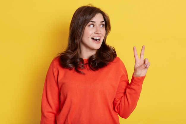Portrait de joyeuse jolie fille souriante portant un pull orange, montrant le signe v avec les doigts