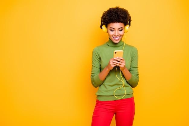 Portrait de joyeuse jolie jolie femme mignonne dans des écouteurs de pantalon rouge écoutant sa mélodie préférée.