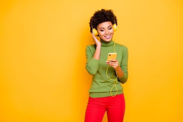 Portrait de joyeuse jolie jolie femme en pantalon rouge col roulé vert bouclés ondulés sourire aux cheveux bruns à pleines dents télécharger sa chanson préférée tout en écoutant.