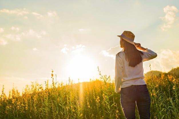 Portrait de joyeuse joyeuse jeune femme heureuse se détendant dans le parc. modèle féminin joyeux respirant de l'air frais à l'extérieur et jouissant de l'odeur dans un jardin fleuri ou un jardin d'été, un ton vintage