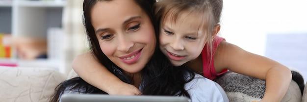 Portrait de joyeuse mère et fille passer du temps ensemble à regarder les enfants montrer sur tablette numérique.