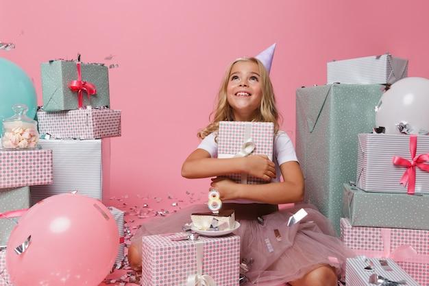 Portrait d'une joyeuse petite fille dans un chapeau d'anniversaire