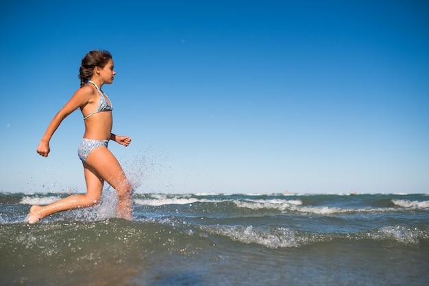 Portrait d'une joyeuse petite fille positive nageant dans la mer par une chaude journée d'été ensoleillée