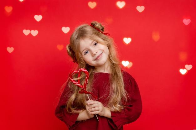 Portrait d'une joyeuse petite fille rêveuse avec un bonbon en forme de coeur dans ses mains isolé sur fond rouge