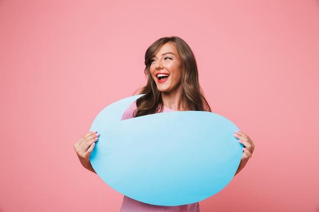 Portrait de joyeuse publicité girl 20s tenant une bannière de pensée bleue vierge avec copyspace pour le texte dans ses mains, isolé sur fond rose
