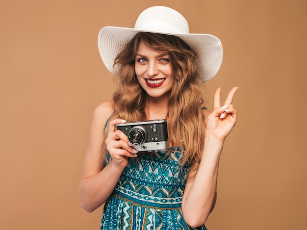 Portrait de joyeuse souriante jeune femme prenant une photo avec inspiration et portant une robe d'été. fille tenant un appareil photo rétro. modèle, poser, chapeau