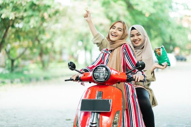 Portrait de joyeuses filles musulmanes équitation scooter profiter des vacances d'été avec des amis