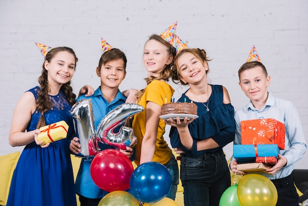 Portrait de joyeux amis adolescents profitant de l'anniversaire en tenant un gâteau d'anniversaire; cadeaux et ballon numéro 14