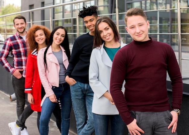 Portrait de joyeux amis multiraciales, regardant la caméra, debout près de la rambarde